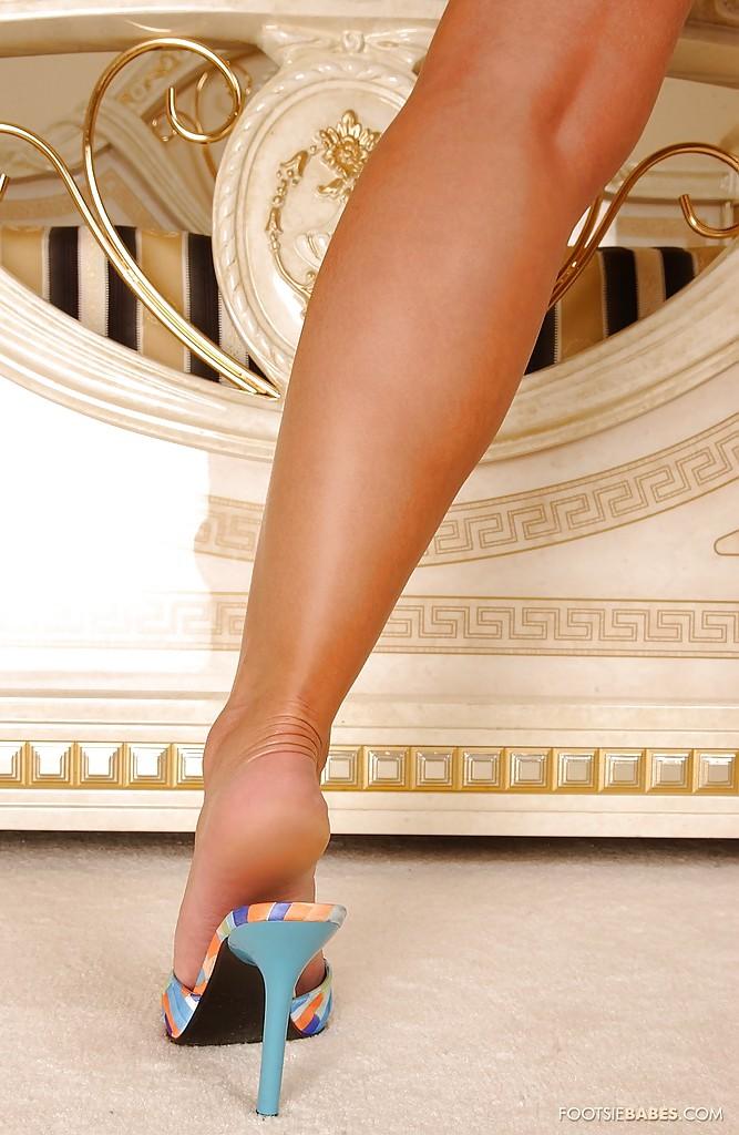 Модель со свелыми волосами Sendy Silver в синей ночнушке выставляет длинные ножки