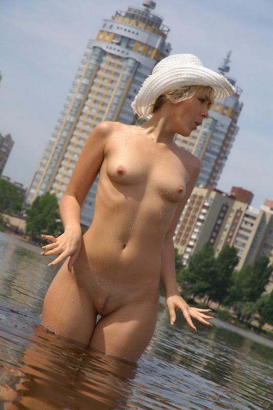 Кучерявая светлая порноактриса фотографируется обнаженная в речке и на тёплом пляже